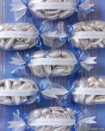 Add sparkle to your reception tables by decorating each place setting with metallic nets filled with foil-wrapped chocolate dragees. The parcels are tied at either end with blue ribbon. Computer-generated labels with blue lettering and borders display the names of the bride and groom as well as the wedding date. Alternatively, labels might list the names of individual guests, allowing the favors to do double-duty as place cards.