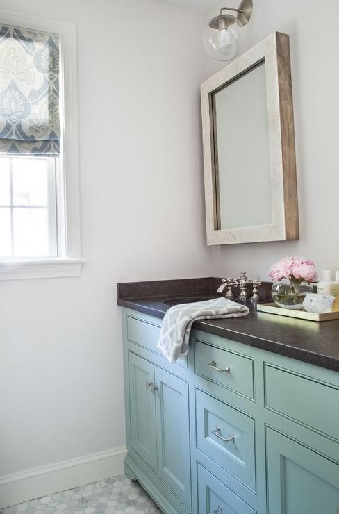 Chic cottage bathroom features a turquoise washstand topped with honed black granite fitted with ...