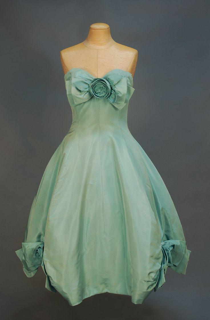 DIOR COUTURE STRAPLESS SILK GALA DRESS, SPRING, 1958. Robin's egg blue faille with sweetheart bodice, built-in boned net corset with hooks & eyes, full skirt over ivory silk and seven layer banded crinoline, ivory silk under skirt, self rose and bow at bodice center front and over gathers at either side of hem, back zipper.