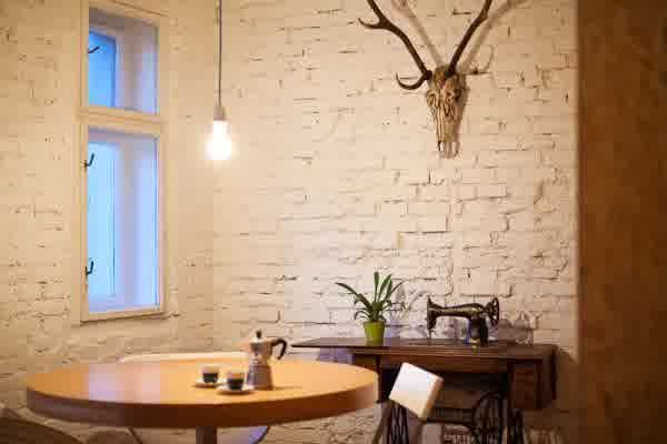 Vintage Scandinavian Office Design with Blackboard Wall Decor: Classic coffee corner in scandinavian office design with rounded wooden table together with antique sewing machine blended with deer head ornament on brick wall