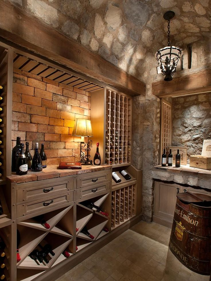 Stone, brick, and wood combine to create this neutral wine cellar filled with rustic charm. A metal pendant light hangs from the ceiling adding to the rooms old world feel. #WineCellar
