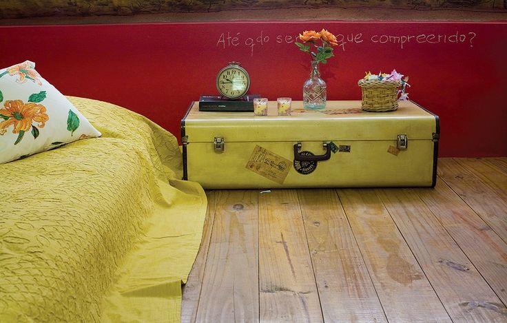 No mezanino do ateliê, a ceramista Gisele Gandolfi instalou seu quarto. Na parede pintada de vermelho ela escreveu uma frase com giz que reflete seu momento atual