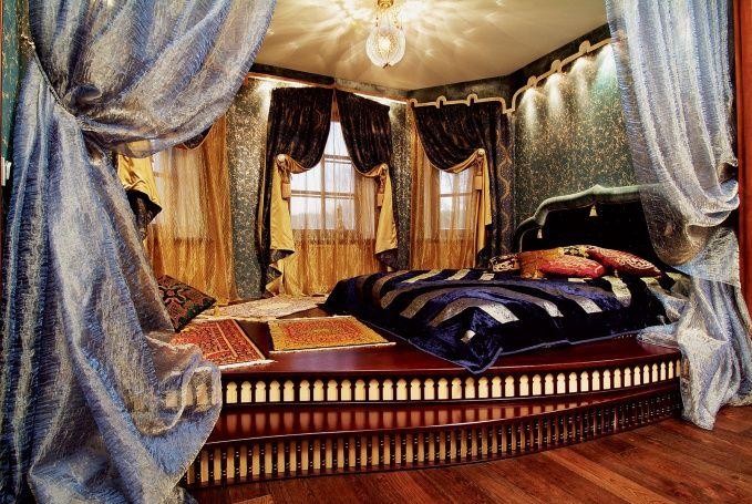 Окна в спальне хозяев задрапированы плотными шторами из шелка и бархата.