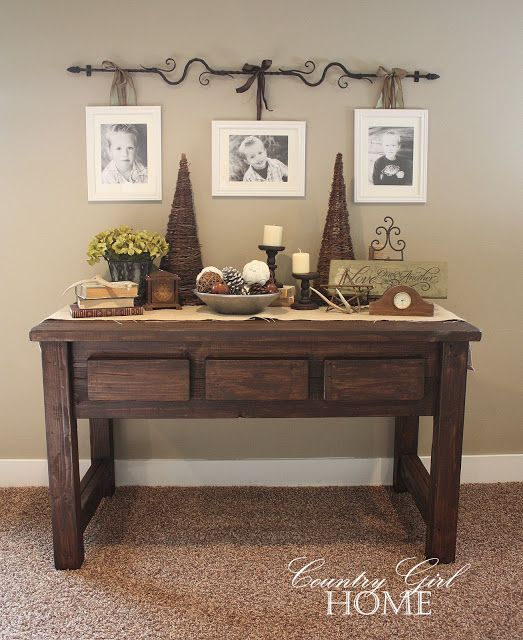 Entry - rustic, dark table (maybe 1/2 round) with bowl and candle decor and curtain rod above hanging pictures, mirror