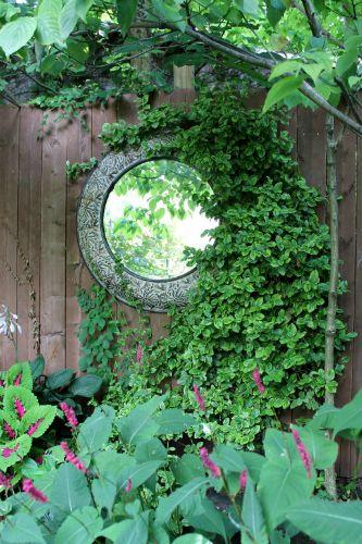 Een spiegel op een muur tussen klimplanten is een geslaagde trompe l'oeil.