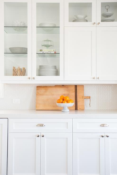 Amazing white kitchen features creamy white shaker cabinets paired with a white marble like quartz countertop, Caesarstone Calacatta Nuvo, and a white mini herringbone tiled backsplash, Ann Sacks Savoy Mosaics Herringbone Tile in Ricepaper.