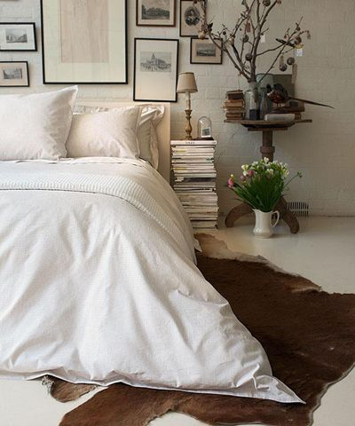 cowhide rug; white linen; framed wall; stacks bedside table.