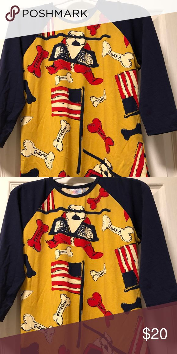 S Lularoe 2017 Americana Randy S Lularoe 2017 Americana Randy. Yellow body with puppy dogs wearing sunglasses waving the American flag and bones displaying patriotic words. Sleeves are navy blue. NWOT. Never worn, perfect condition. LuLaRoe Tops Tees - Long Sleeve