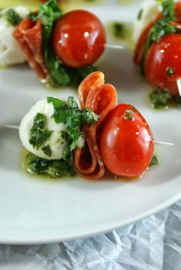 Mini brochetas de tomate cherry con una bolita de queso mozzarella y pepperoni bañadas en aceite de oliva y hojas de albahaca