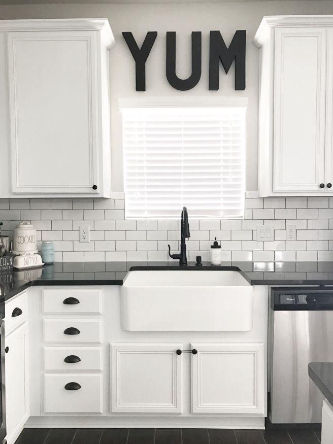 Black, White and Teal Kitchen. Farmhouse Sink. SOURCE: lollipopsandlightsabers black and white, modern farmhouse, farmhouse sink, subway tile, black granite, black hardware, white cabinets, whirlpool appliances, teal pantry door, fresh pies, rae dunn, YUM.