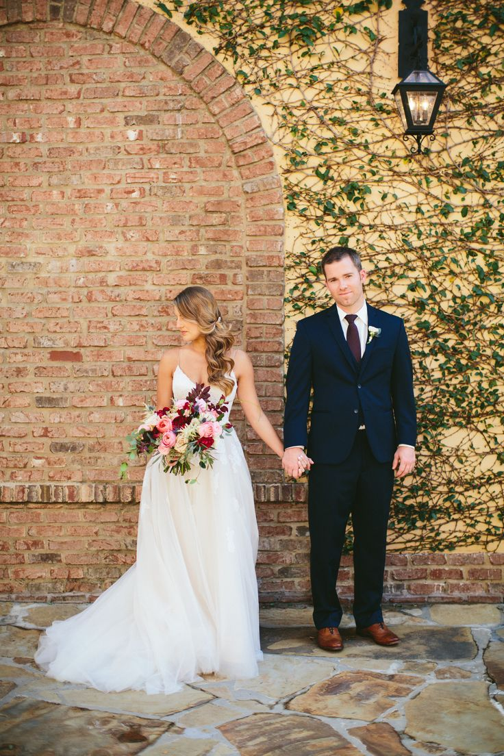 an autumn bride and groom pose in front of a vine covered brick wall. the bride clutches her lush and loose bouquet of burgundy peony, pink garden roses, blush spray roses, pink ranunculus, peach stock, blue thistle, vines and greenery.