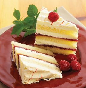TOO TALL® WHITE CHOCOLATE RASPBERRY CAKE. This magnificent cake of white chocolate whipped cream icing, soft shortcake, a sweetly tart raspberry filling, and red and white chocolatey drizzles reaches its height of flavour when served slightly chilled. - M & M Meat Shops
