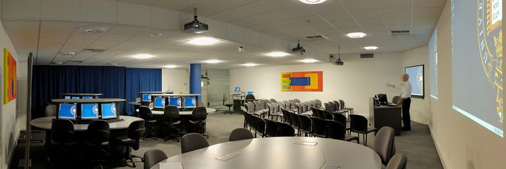 OThe lecture style area seats about forty. In the rest of the room there are five oval tables each seating six students in front of a computer.  The centre sections of the desks are motorised to lower the computers into the desk and so provide a flat surface (see the nearest desk in the image). Eight students can then sit around each table for seminar-style group working. When necessary, the desks can be unplugged from mains and data sockets in the floor and pushed to the rear of the room…