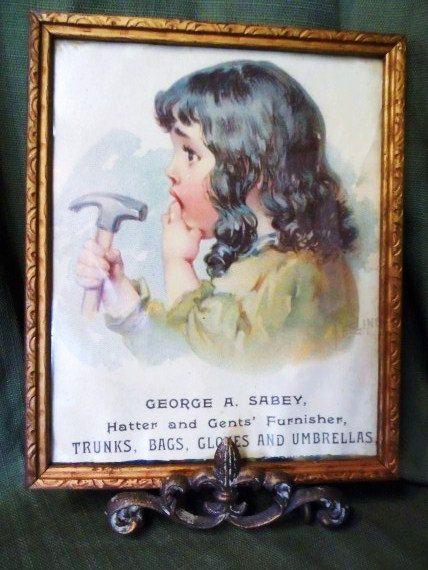Old Color Framed Advertising Print- Girl & Hammer Labled FEELING-George A. Sabey Hatter and Gents' Furnisher Trunks, Bags, Gloves ,Umbrellas...