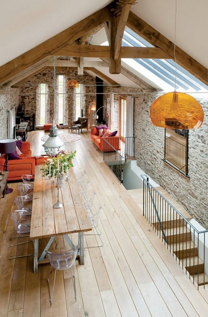 Wonen in een oude kerk. Hier is een bovenverdieping gemaakt die volledig is ingericht als moderne leefruimte met zithoek en grote eettafel. Bijzondere houten balken, hoge ramen en stenen muren van vroeger.