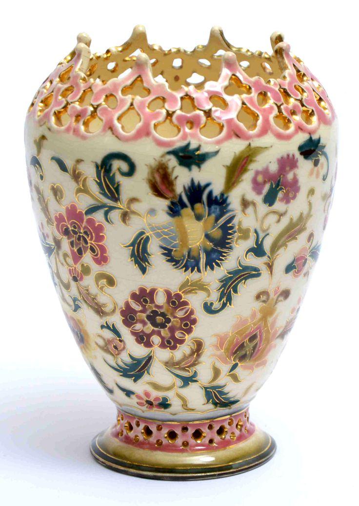 Zsolnay díszváza Porcelánfajansz. Áttört peremén és felületén magas tüzű, színes mázakkal  festett és aranyozott perzsa dekor. Alján jelzett: masszába nyomott 1611 (formaszám), valamint máz alatt kékkel bélyegzett családi jegy, arannyal 57 (aranyozó mester száma) Zsolnay, Pécs, 1880 körül. Magasság: 18,5 cm Zs16/61e