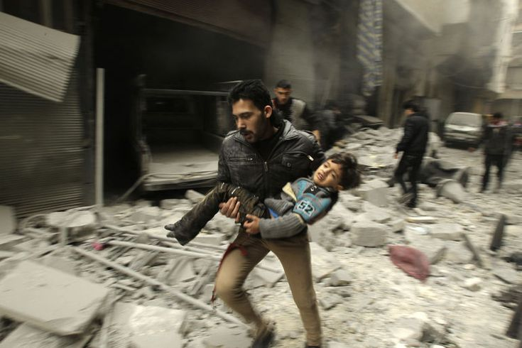 A man runs as he carries a child who survived from what activists say was an airstrike by forces loyal to Syrian President Bashar al-Assad, at al-Ferdaws in Aleppo on Jan. 21, 2014.