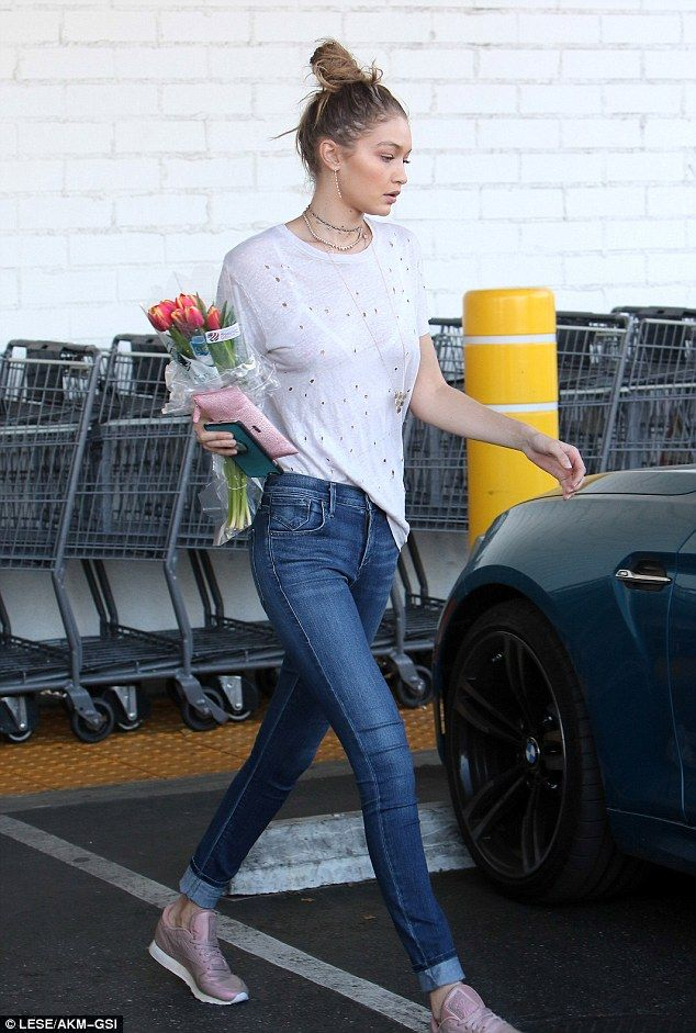 Pretty:Gigi looked good in a thin cotton T-Shirt featuring holes all over it along with skinny blue jeans pin-rolled to show off her ankles and a pair of pink Reebok Classic trainers