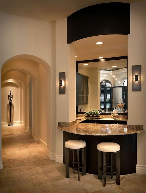 LOVE the stone tiled flooring and the marble top kitchen counter plus the sconce lighting on either side of the counter top.