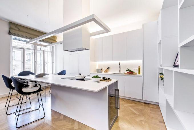Kuchyňská sestava nábytku je vyrobena na míru z bílé MDF desky. pouze pracovní deska a stěna za ní je zhotovena z umělého kamene technistone. Jídelní stůl s ostrůvkem doplňují o 13 cm vyšší, speciálně upravené židle Elephant značky Kristalia