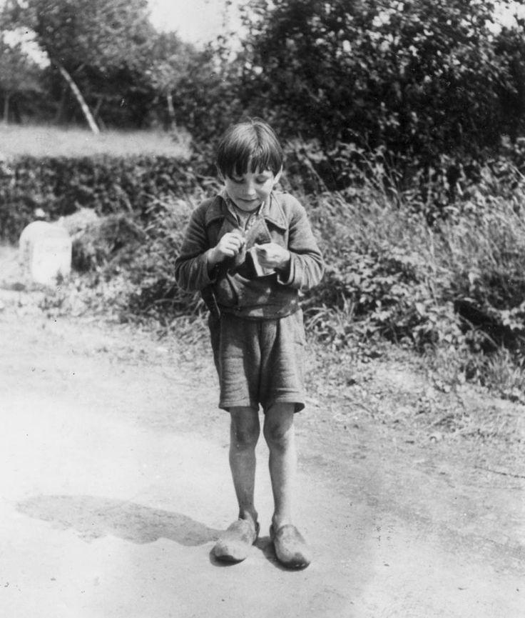 IlPost - 1944. Un bambino francese mangia la cioccolata regalata dai soldati americani (Robert Capa/Keystone/Getty Images)