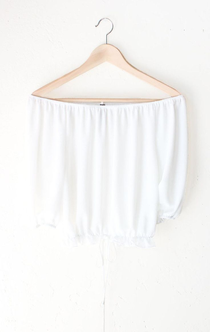 - Description Details: Off-the-shoulder half sleeves crop top in white featuring an elasticized neckline & self tie accent on the ruffled elasticized hem. Flowy, relaxed fit. Measurements (Size Guide)