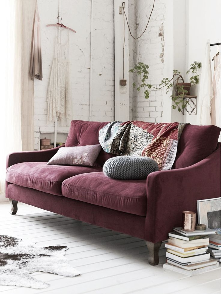plum sofa and white brick walls