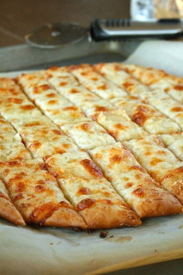 Pizza deeg met knoflookboter en kaas. Maak pizzabodem (kan ook als een grote rechthoek op de ovenbakplaat) smeer er knoflook/kruidenboter over, strooi er geraspte parmezaanse kaas en geraspte mozzarella over, een snufje zout en peper.. afbakken in de oven, in mooie reepjes snijden als borrelhapje