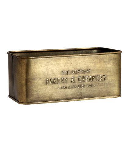 Guld. En rektangulär förvaringslåda i metall med präglad text. Storlek 10,5x12x25 cm.