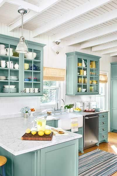 Beach cottage kitchen remodel with teal custom kitchen cabinets with paneled glass fronts, white subway tile backsplash, gray and white carrara marble countertops, and classic white painted shiplap walls and beams in the ceiling, all with fresh pops of yellow throughout.