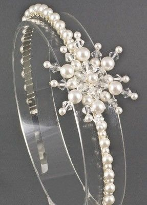 The Grande Icy Snowflake headband is perfect for a midwinter wedding, a large embellished snowflake made with a mixture swarovski bicone crystals and pearls of various sizes positioned to the side of a pearl beaded band.