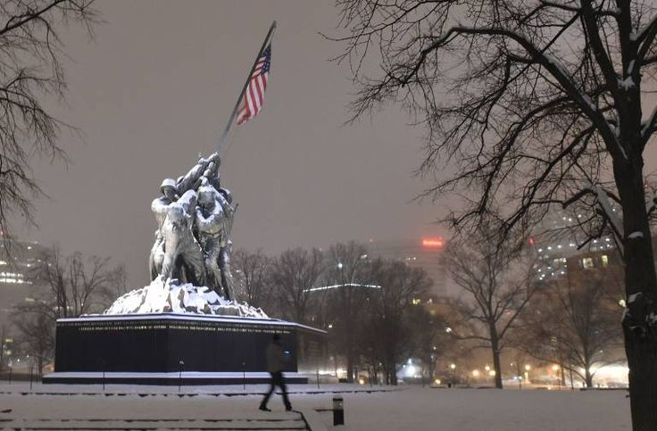 A man walks in the snow in front of the Iwo Jima memorial in Washington DC 2/17/2015