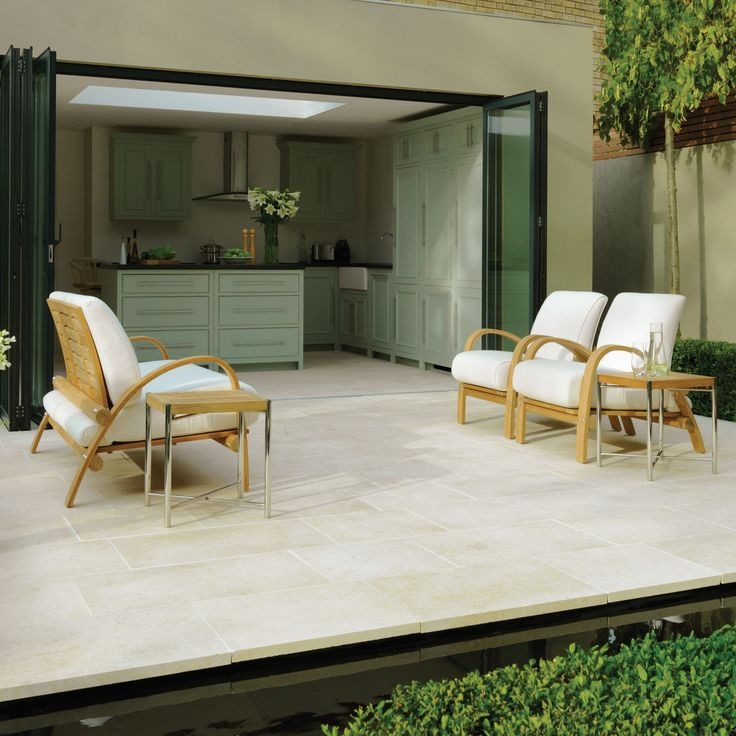 patio stone paved patio terrace running continued into kitchen | bi-fold doors open onto courtyard garden | narrow rill surrounding patio | Stonemarket- Limestone 'Isis range'- Delta Sand- QUESTION: does anyone know the designer please?