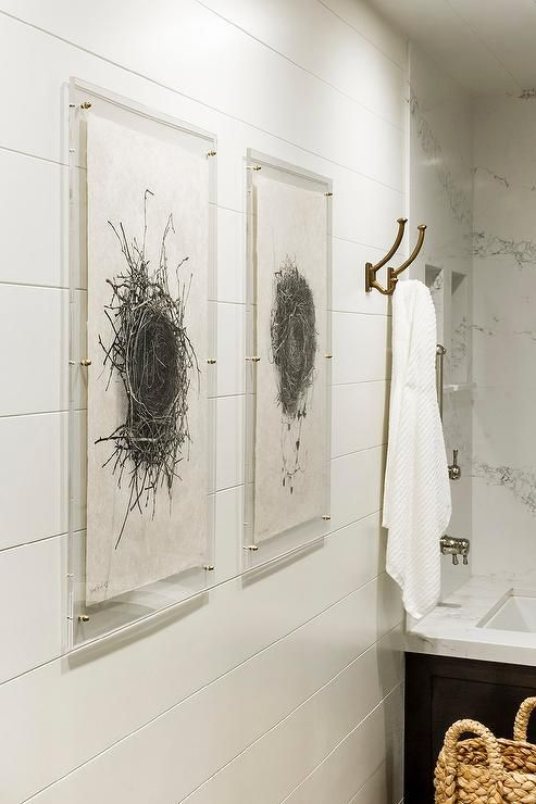 A set of sepia birds' nest art prints are encased in acrylic picture frames lining a shiplap bathroom wall.