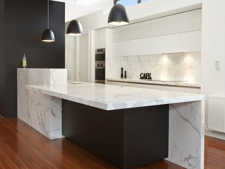 "MODERN MAGNIFICENCE    80mm thick huge marble island 4700 x 1200 bench top.  Overhead cabinets Blum motorised lift ups. Handless using aluminium extrusion.  Marble splash back.  Features dark colour ""Bitter Black"""