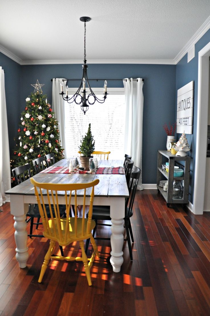 Farmhouse dining room decorated for Christmas. I like that idea of having a tree in the dining room. I like the blue wall as well!
