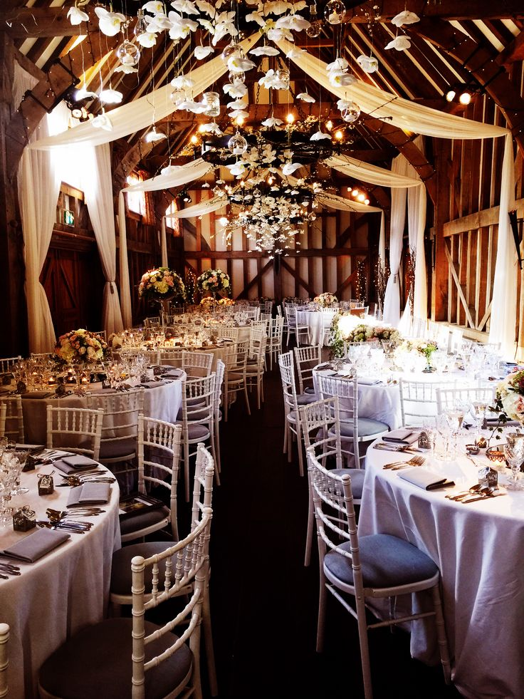Muslin beam drapes, white trevira doorway drapes, twisted willow clusters with pealights, and LED wall uplighters at Gate Street Barn by www.stressfreehire.com #venuetransformers