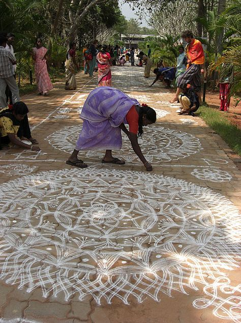 """""""rangoli"""" is a traditional mandala, a geometric pattern, that women design in front of their houses during festivities. In Tamil culture is a strong form of expression by the women. This festival takes place in Bharat Nivas, the """"Indian culture and spirit"""" pavilion of Auroville's International zone, every year soon after the Pongal festivities. Hundreds of women gather from Auroville and the nearby villages to show their skills in this particular art."""