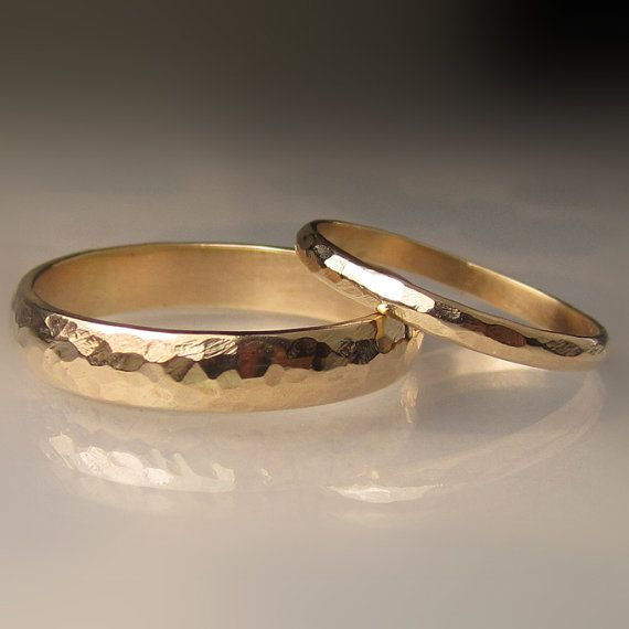 Hand forged hammered wedding band set in recycled half round 10k yellow gold. Ladies ring is approx. 2mm wide X 1mm thick and mens…