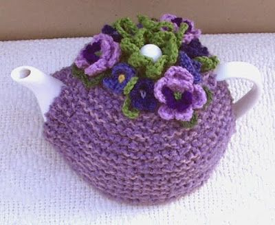 Groovy Textiles: Knitted tea cosy with gorgeous crochet pansies.  I love this one.  Looks simple enough, I just need to find the pansy pattern.