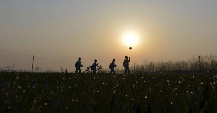 Alunos brincam com bolas de futebol durante seu trajeto até o Centro de Ensino Fundamental Sunji, na província de Shandong, na China