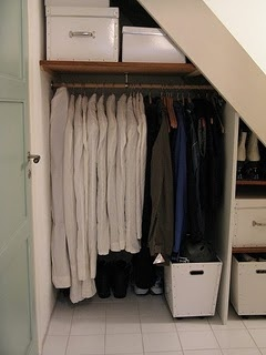Under stairs coat closet with rolling bins on the floor. Nice for my basement