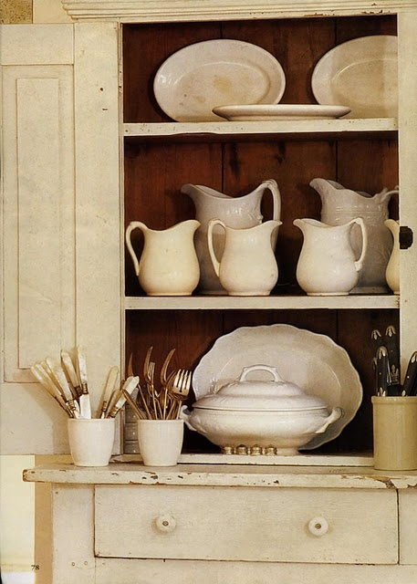 White ironstone pitchers and platters, wonderful large soup tureen in white cupboard.