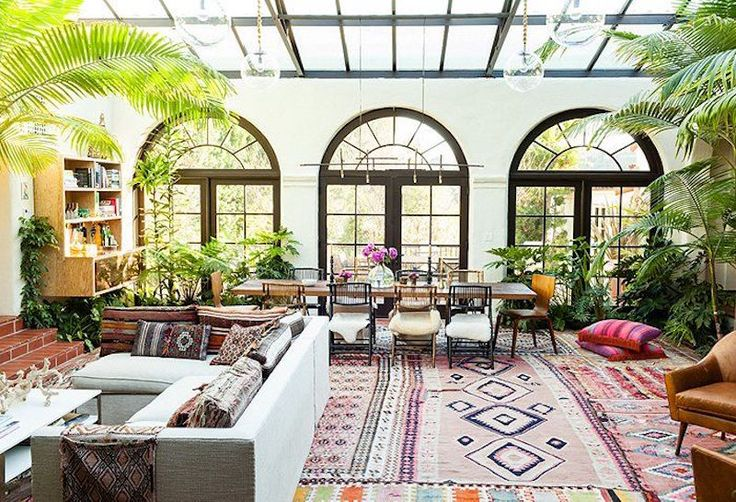 Eclectic living space with aztec rugs and indoor plants.