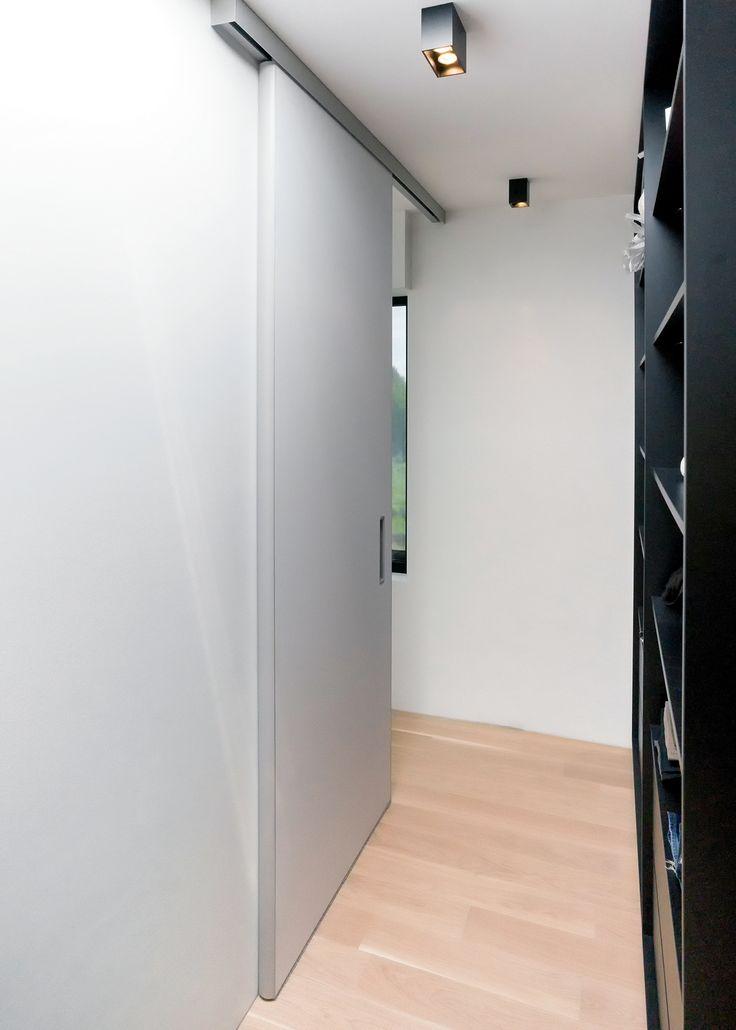 schuifdeur van vloer tot plafond met aluminium bovenrail zonder zichtbare geleiding op de vloer.
