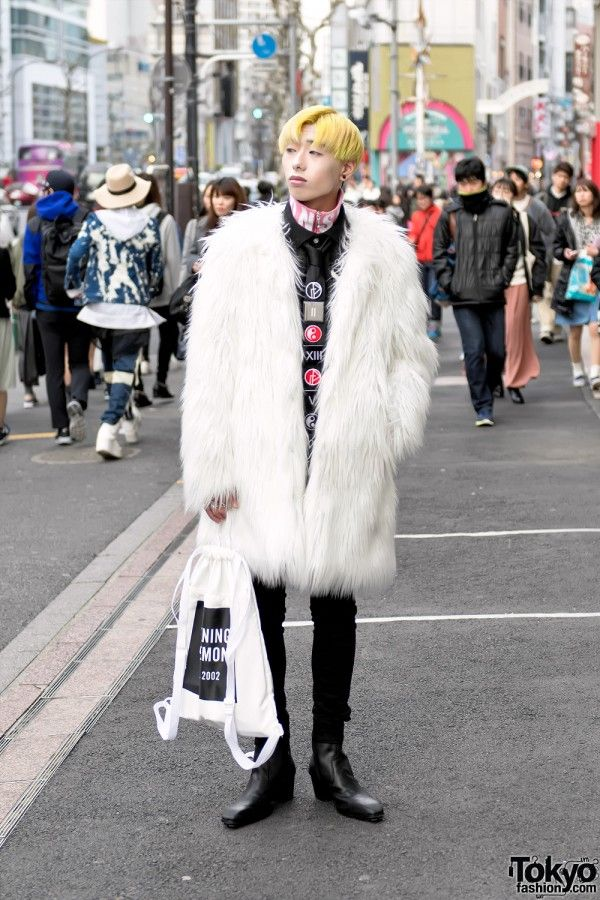 Manaya's street style includes a large faux fur coat by the Japanese brand Kawi Jamele over layered tops from American Eagle and Christopher Shannon, UNIQLO skinny jeans, and Yosuke black leather boots. His handbag is from Opening Ceremony and other accessories are by Christian Dada and Gosha Rubchinskiy.
