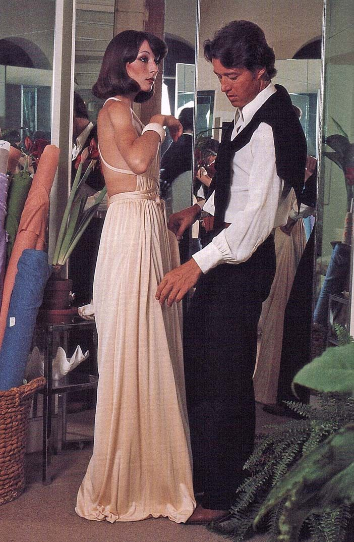1970s evening dress. Above is am image of Halston fitting a young Angelica Houston in one of his signature evening designs. Evening dresses of the 1970s were typically long, flowing, and exposed significant skin on the upper body.