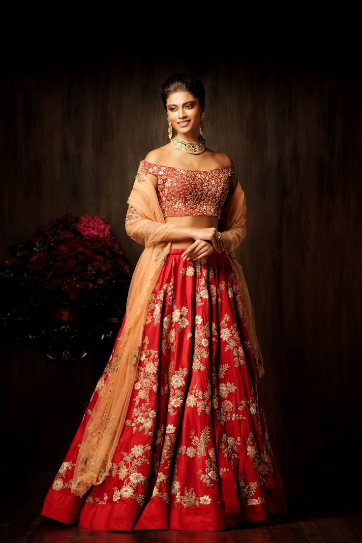A ribbon red bias cut lehenga with zardosi and resham thread floral buttas, complete with a rich silk border at the hem, teamed with an aurora red off shoulder blouse, truly modern in its intricate floral thread and peeta embroidery. Fit for the new age bride, looking to juxtapose tradition and contemporary trends, this red lehenga look is finished with a light peach tulle dupatta. #bridal #trends #bridal2017 #bridalfashion #bridaldress #weddinglehenga