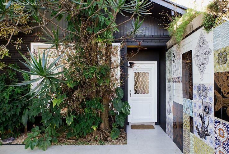 A entrada do ateliê da artista Calu Fontes tem painel de azulejos e fachada com tijolinhos pintados de preto.