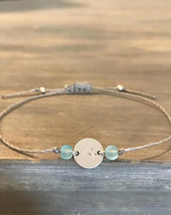 Description: Silver Wave Bracelet - The epitome of beach inspired, this delightful bracelet is made with durable waxed Linhasita thread, a silver disk hand stamped with a wave, and two seafoam blue sea glass beads on either side secured with knots. The bracelet is made adjustable with a sliding knot closure and the ends are finished off with two Toho Silver Seed Beads  Overview: This crave worthy, beach inspired bracelet makes the perfect gift for yourself and others! The matte silver disk…